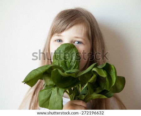 Happy little girl holding a bunch of spinach, white background - stock photo