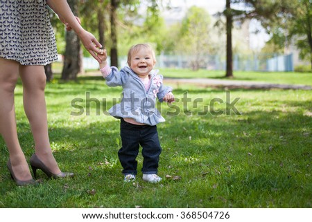 Happy little girl holding mothers hand