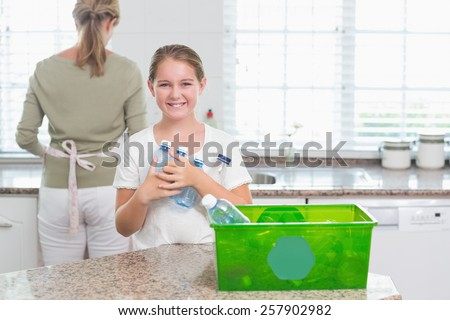 Happy little girl holding recycling bottles at home in the kitchen - stock photo