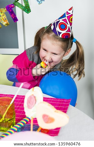 Happy little girl how have fun in a birthday party