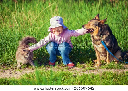 Happy little girl hugging dog and cat outdoors