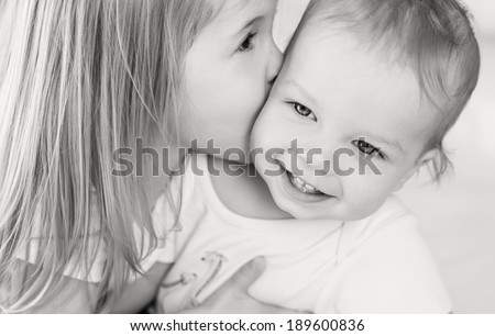 happy little girl hugging kissing his brother ( black and white ) - stock photo