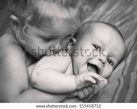 happy little girl hugging kissing his brother (black and white image) - stock photo