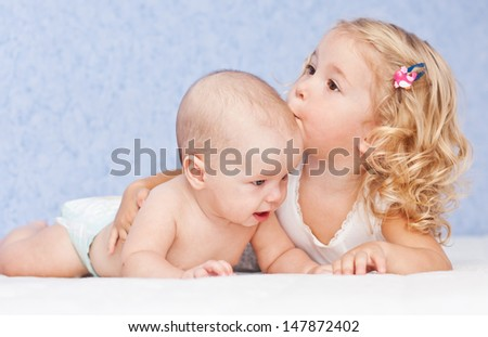 happy little girl hugging kissing his brother on a blue background - stock photo