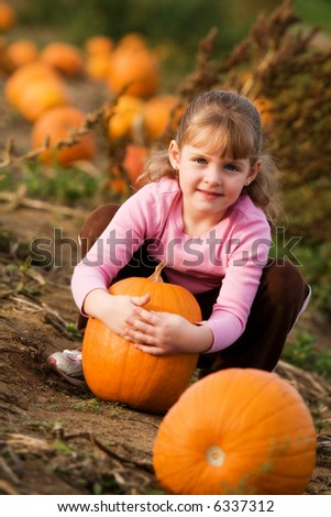 Happy little girl hugging the pumpkin she's selected from a pumpkin patch.