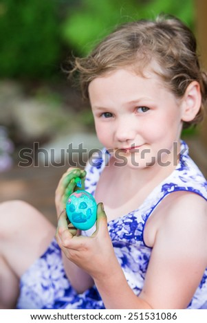 Happy little girl in a pretty dress smiles and decorates a color dyed Easter egg with paint while outdoors in the garden setting during the springtime.  Selective focus on the Egg.  Part of a series.  - stock photo