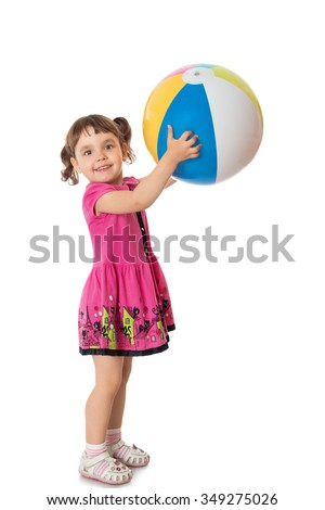 Happy little girl in a short pink dress throws a big striped ball - Isolated on white background - stock photo