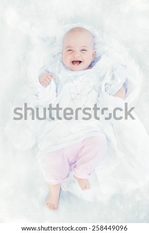 happy little girl in a white shirt on white cloth