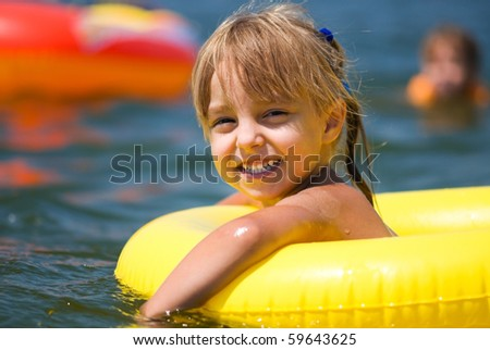 Happy little girl in a yellow ring has fun in the sea - stock photo
