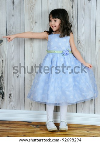 happy little girl in beautiful blue dress pointing at something - stock photo