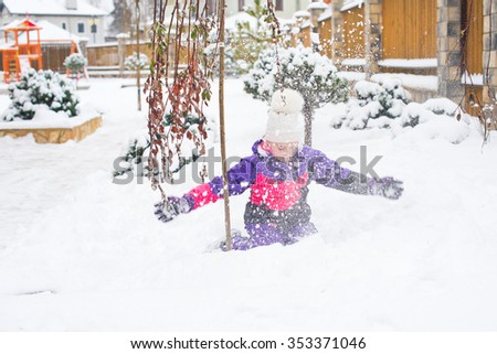 Happy little girl in colorful suit and white hat play with snow in back yard of village country house in cold winter weather - stock photo