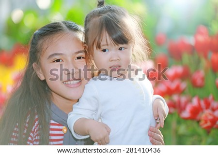 Happy little girl in flower field - stock photo
