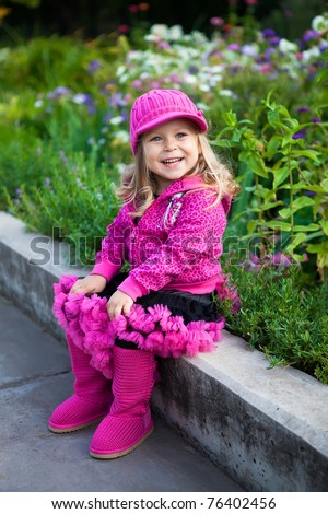 happy little girl in flower garden - stock photo