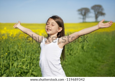Happy little girl in front of canola field - stock photo
