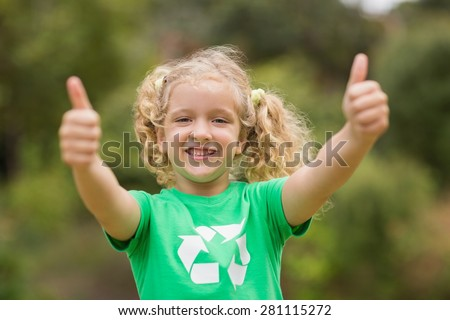 Happy little girl in green with thumbs up on a sunny day - stock photo