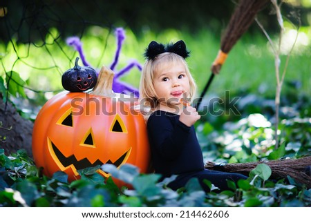 Happy little girl in halloween costume with jack pumpkin, tick or treat - stock photo