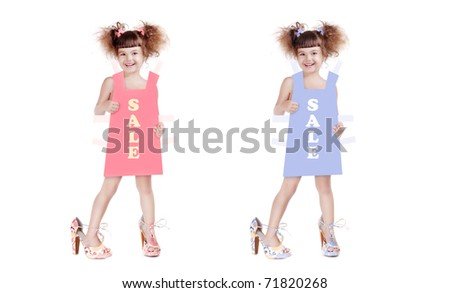 Happy little girl in mom's shoes holding a paper dress with sale inscription  in front of her
