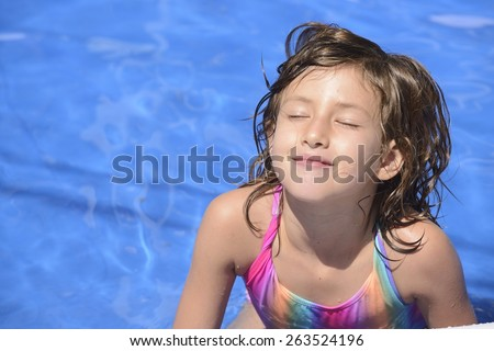 Happy little girl in outdoor sunny day swimming in the pool. - stock photo