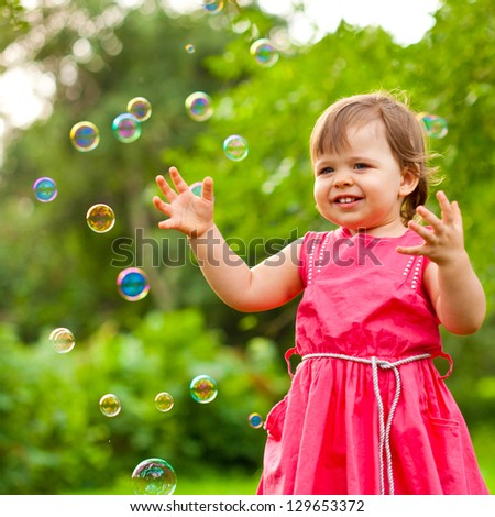 happy little girl in pink dress at park with flying soap bubbles