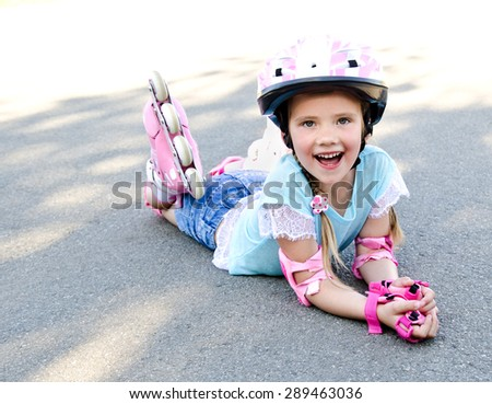 Happy little girl in pink roller skates and protective gear outdoor - stock photo