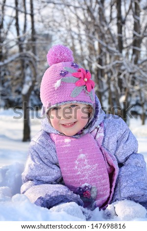 Happy little girl in pink scarf and hat lies in snow and looks away outdoor in winter.