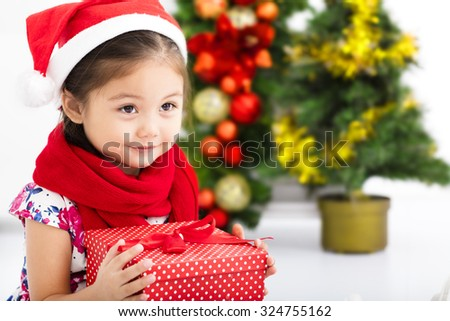 happy little girl  in Santa red hat and holding Christmas gift - stock photo