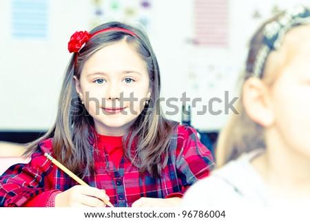 Happy little girl in school with her friends arround - stock photo