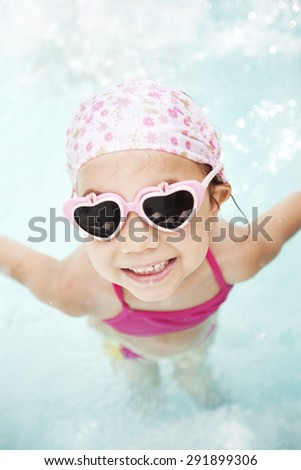Happy little girl in swimming pool - stock photo