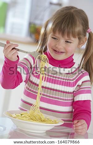 Happy little girl is eating spaghetti,  - stock photo