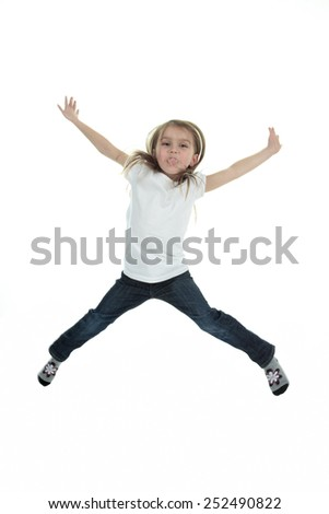 Happy little girl is jumping against white isolated background
