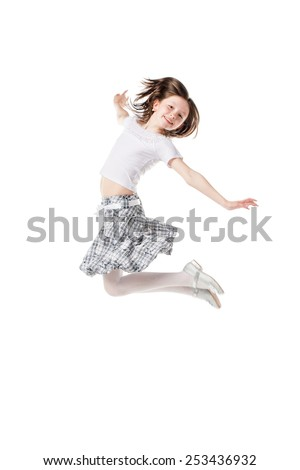 Happy little girl jumping against white background - stock photo