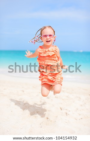 Happy little girl jumping at tropical beach