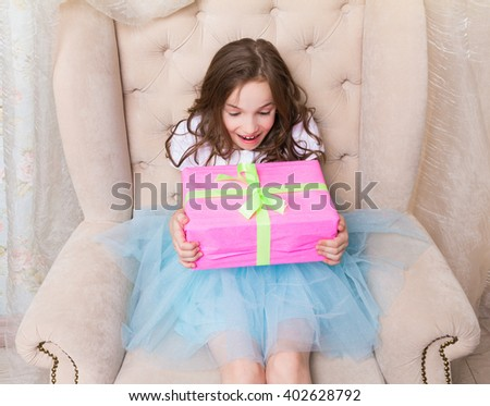 Happy little girl just got her present - pink gift box with ribbon and bow - stock photo