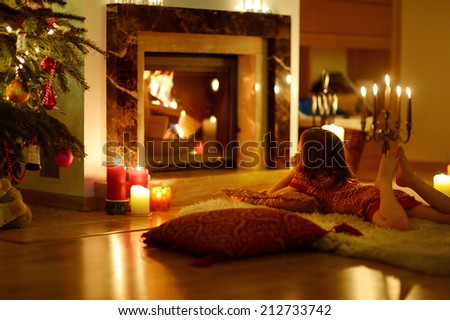 Happy little girl laying by a fireplace in a cozy dark living room on Christmas eve - stock photo
