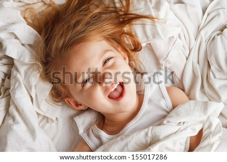 Happy little girl laying in white laundry - stock photo