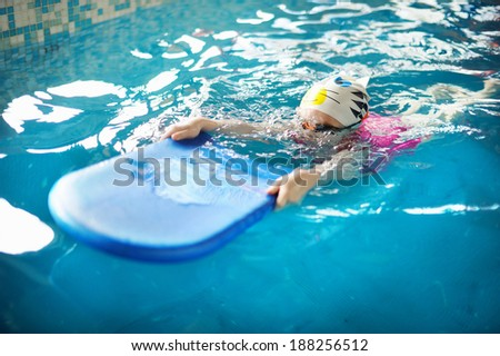 Happy little girl learning to swim in a pool - stock photo