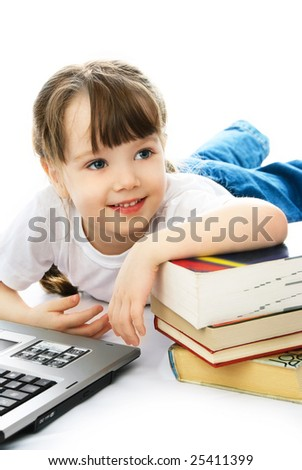 happy little girl lies on the floor with books and a laptop