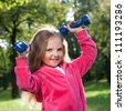 Happy little girl lifting dumbbells in park outdoors - stock photo