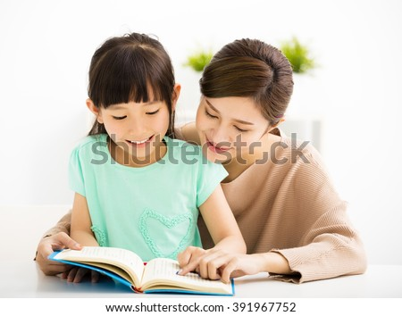 happy Little girl looking at book  with her mother - stock photo