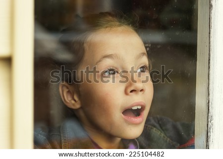 happy little girl looking through an old window - stock photo