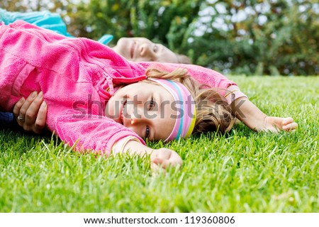 Happy little girl lying on grass, her mother behind - stock photo