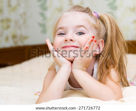 Happy little girl lying on the bed - stock photo