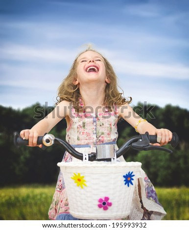 Happy little girl on a bicycle in the park. - stock photo