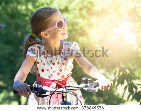 Happy little girl on a bike - stock photo