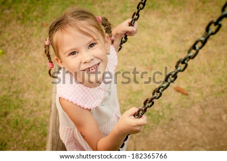 happy little girl on a swing - stock photo