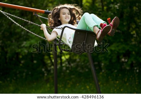 Happy Little girl on a swing in the summer park - stock photo