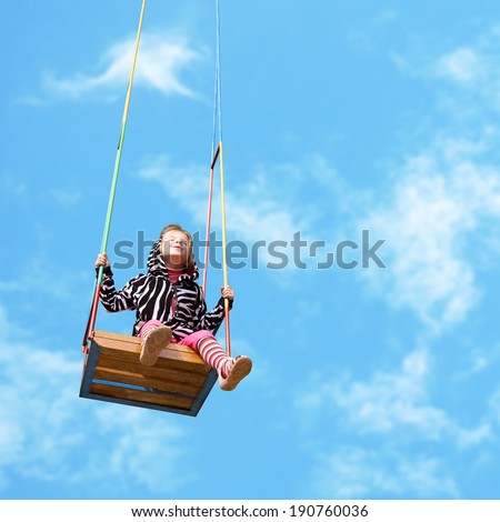 happy little girl on a swing on sky background - stock photo
