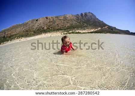 Happy little girl on greek island beach - stock photo