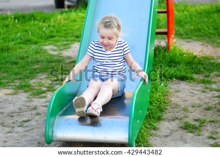 Happy little girl on slide in summer park