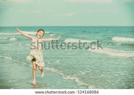 Happy little girl on the beach retro style